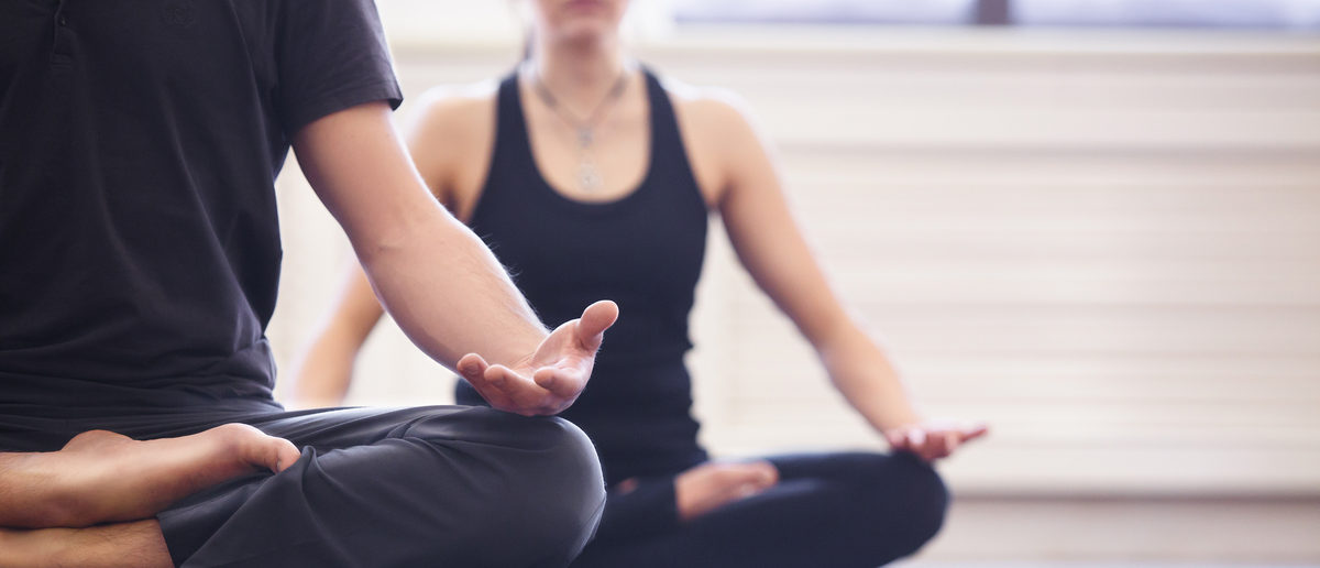 Yoga group concept. Young couple meditating together, sitting back to back on windows background, copy space Shutterstock/ZephyrMedia | Pro-Second Amendment Yoga Pants On Sale