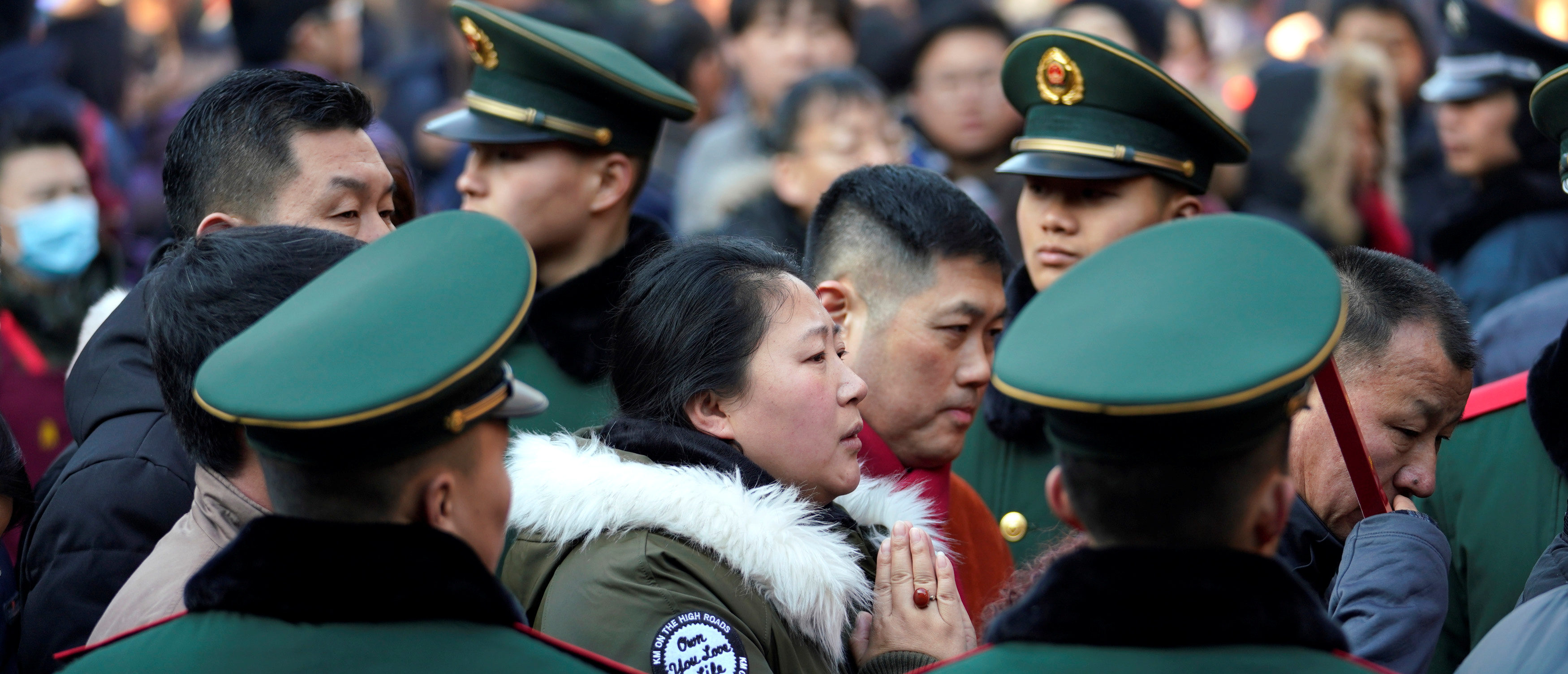 People crowd through paramilitary police officers to enter a hall to pray for good fortune at Lama Temple on the first day of the Year of the Dog in Beijing, China February 16, 2018. REUTERS/Jason Lee - RC1176280890
