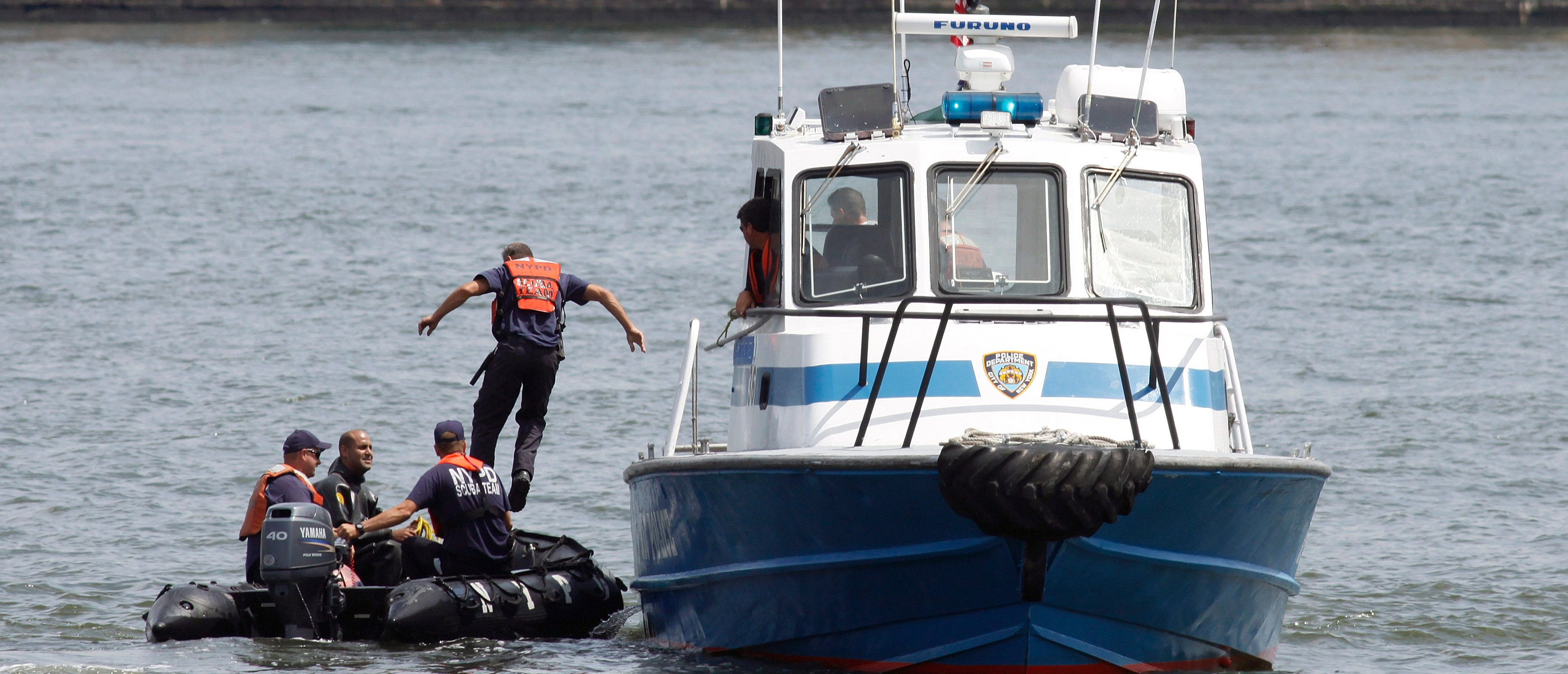 A NYPD scuba team is on site of a crash between a helicopter and an aircraft over the Hudson River, between New York and Hoboken, New Jersey, August 8, 2009. The tour helicopter collided with the small plane in midair and both crashed into the Hudson River near lower Manhattan, police reported on Saturday. REUTERS/Gary Hershorn