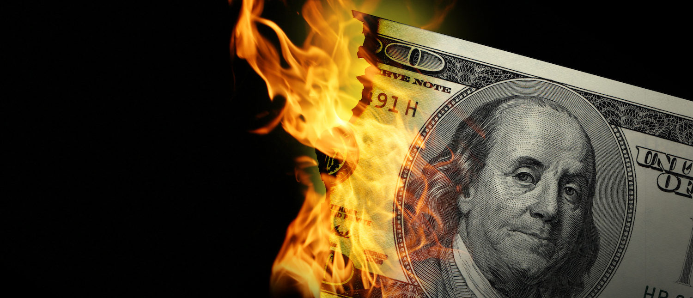 Burning dollars close up over black background. (Shutterstock/bioraven)
