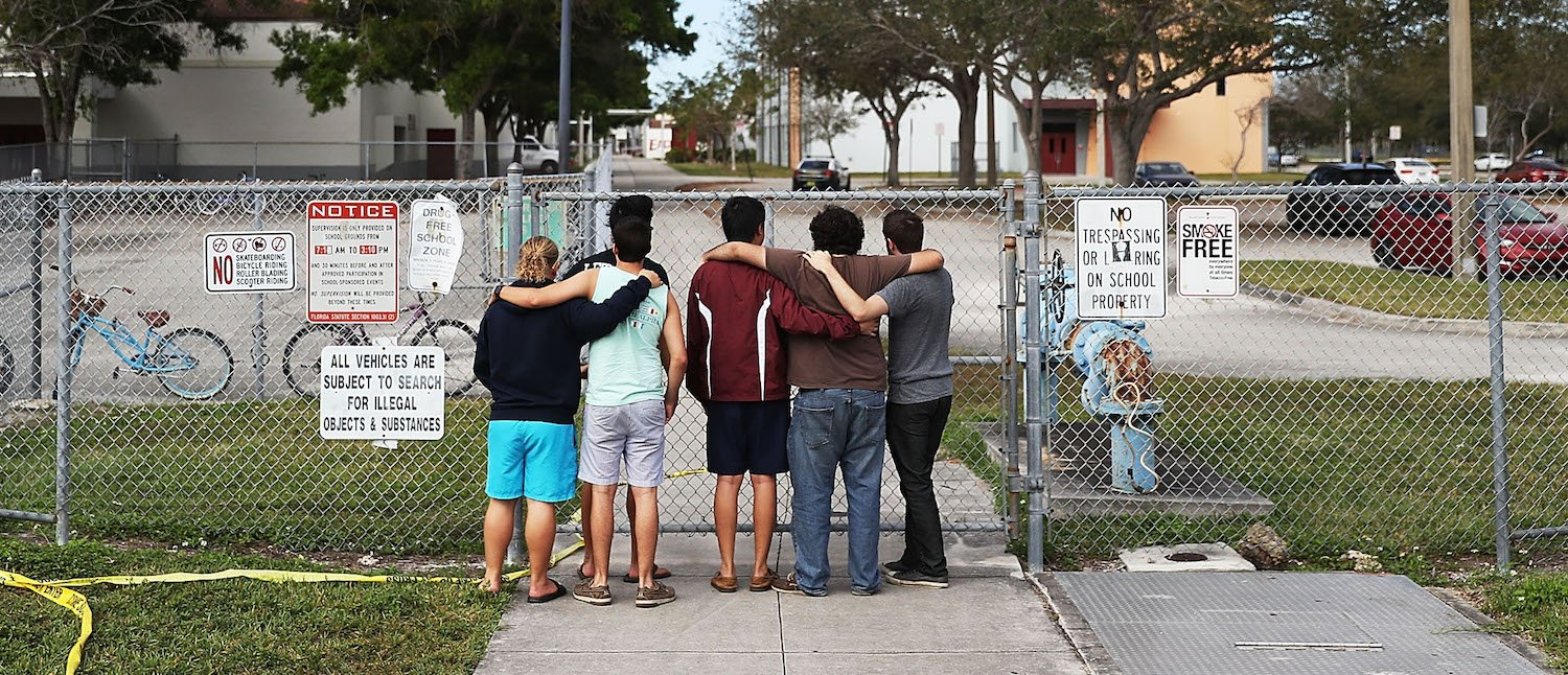 People look on at the Marjory Stoneman Douglas High School on February 18, 2018 in Parkland, Florida. (Photo: Joe Raedle/Getty Images)