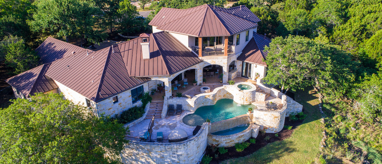 Rich Luxury mansion on large lot of land with Texas hill country landscape and surrounding green surroundings of the ranch country home with infinity pool and wealthy real estate living. (Shutterstock/Roschetzky Photography)