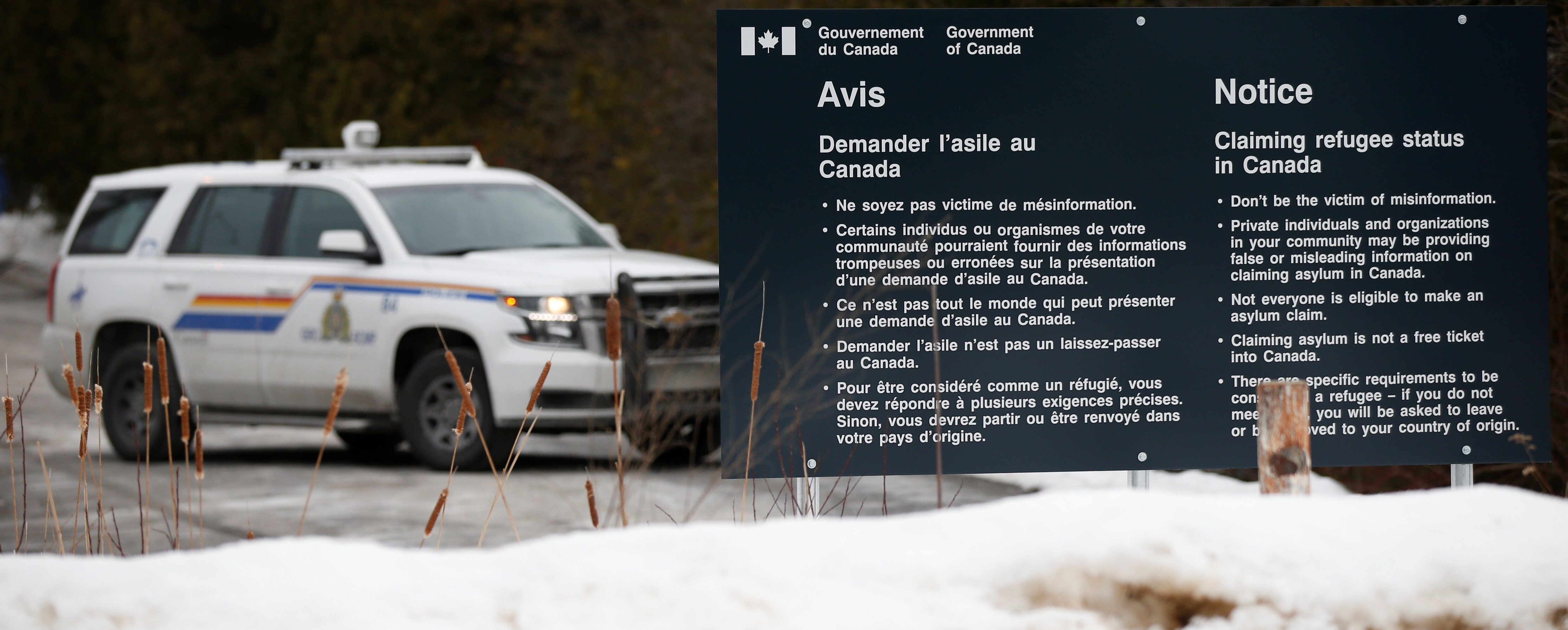 A Royal Canadian Mounted Police (RCMP) vehicle is seen near a sign at the US-Canada border in Lacolle, Quebec, Canada, February 14, 2018. REUTERS/Chris Wattie
