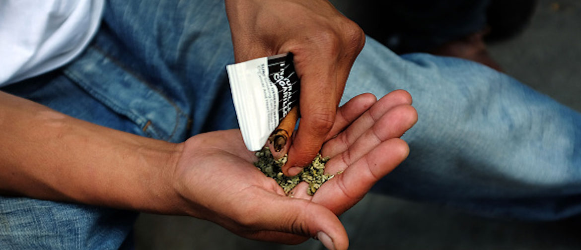"""NEW YORK, NY - AUGUST 05: A man prepares to smoke K2 or """"Spice"""", a synthetic marijuana drug, along a street in East Harlem on August 5, 2015 in New York City. New York, along with other cities, is experiencing a deadly epidemic of synthetic marijuana usage including varieties known as K2 or """"Spice"""" which can cause extreme reactions in some users. According to New York's health department, more than 120 people visited an emergency room in the city in just one week in April. While the state banned the ingredients used to make K2 in 2012, distributors have switched to other ingredients and names in an attempt to circumvent the law. (Photo by Spencer Platt/Getty Images)"""