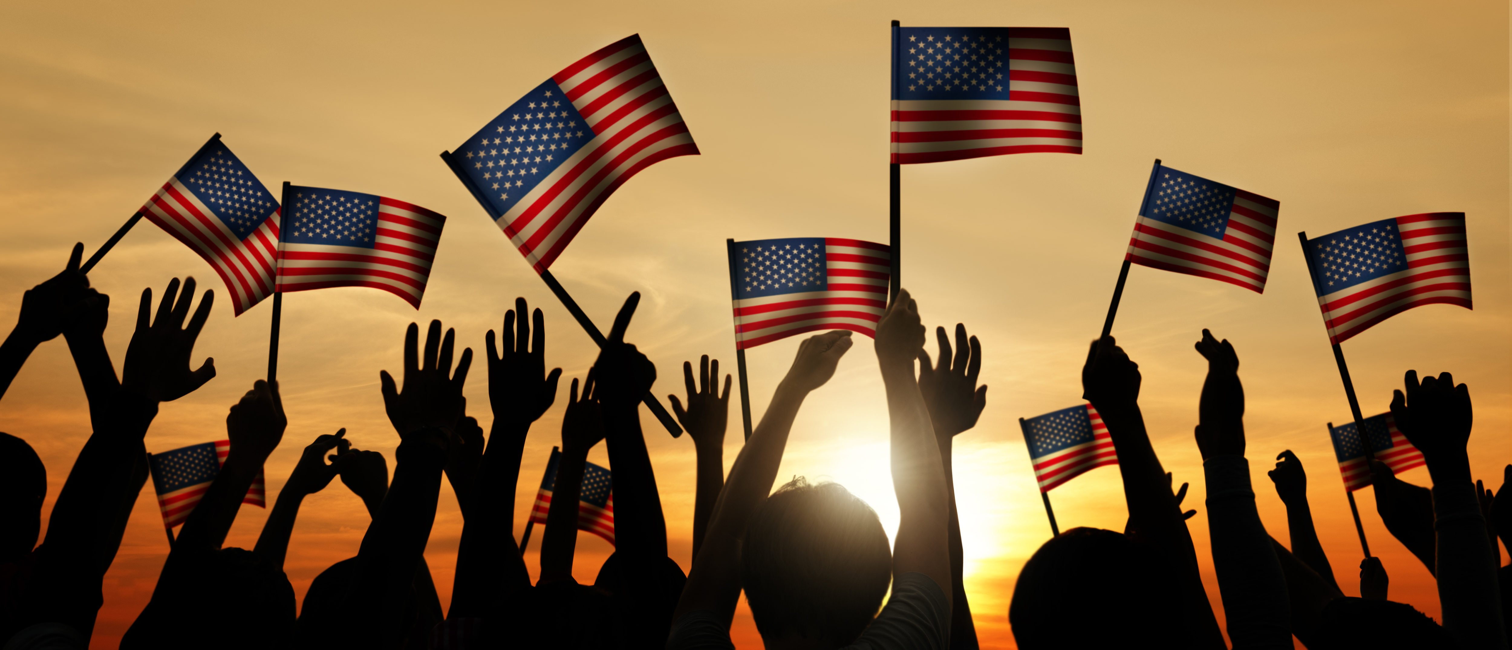 Group of People Waving American Flags in Back Lit. Shutterstock