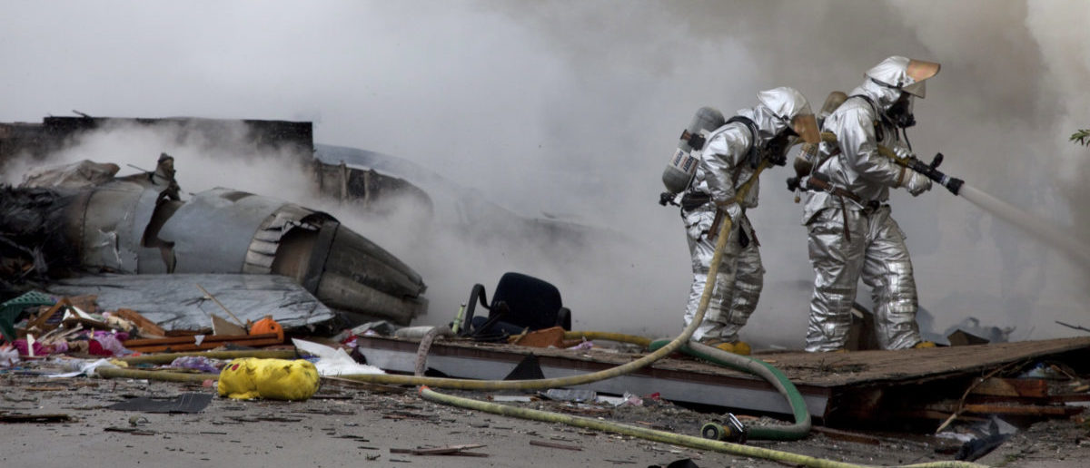 Firefighters battle flames next to the remains of a military jet that crashed into homes in the University City neighborhood of San Diego, California December 8, 2008. The military F-18 jet crashed on Monday into the California neighborhood near San Diego after the pilot ejected, igniting at least one home, officials said. REUTERS/Fred Greaves