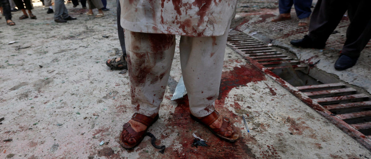 A man stained with blood inspects at the site of a suicide bomb attack in Kabul, Afghanistan April 22, 2018.REUTERS/Omar Sobhani | ISIS Bomber Butchers Dozens In Kabul