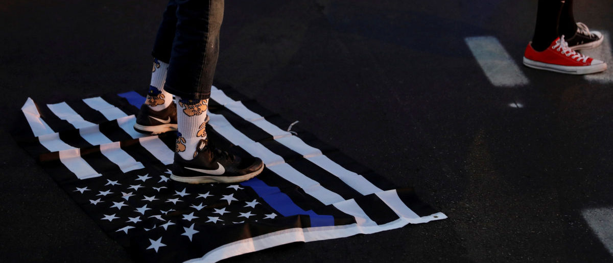 "A protester stands on a ""Blue Lives Matter"" flag after the not guilty verdict in the murder trial of Jason Stockley, a former St. Louis police officer, charged with the 2011 shooting of Anthony Lamar Smith, who was black, in St. Louis, Missouri, U.S., September 15, 2017. REUTERS/Whitney Curtis"