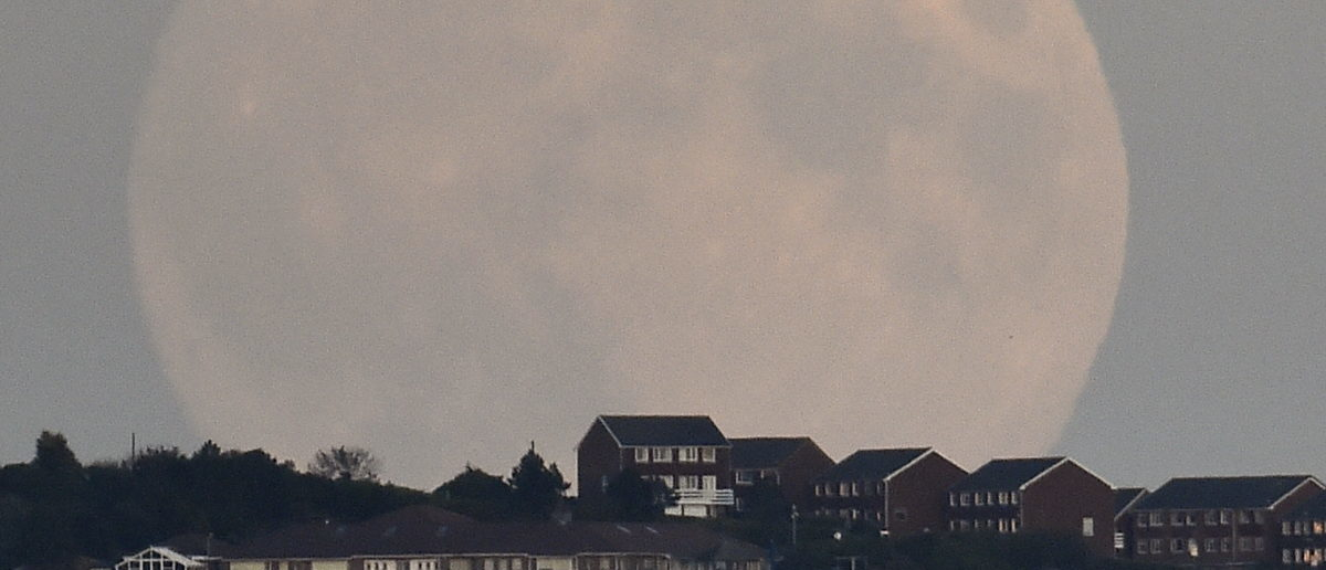 """A """"supermoon'' rises above Brighton in southern England September 27, 2015. Sky-watchers around the world are in for a treat Sunday night and Monday when the shadow of Earth casts a reddish glow on the moon, the result of rare combination of an eclipse with the closest full moon of the year. The total """"supermoon"""" lunar eclipse, also known as a """"blood moon"""" is one that appears bigger and brighter than usual as it reaches the point in its orbit that is closest to Earth. REUTERS/Toby Melville"""