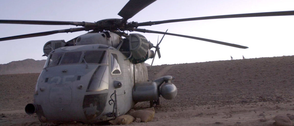 """A U.S. Marine Corps CH-53 Super Stallion sits idle after it had a """"hard landing"""" northwest of the city of Kandahar, Afghanistan. [Marines are beginning the recovery process and hope to fly the damaged helicopter out of the rugged terrain and back to the Marine's base of operations at Kandahar International Airport. Picture taken December 30, 2001. REUTERS/Stringer"""