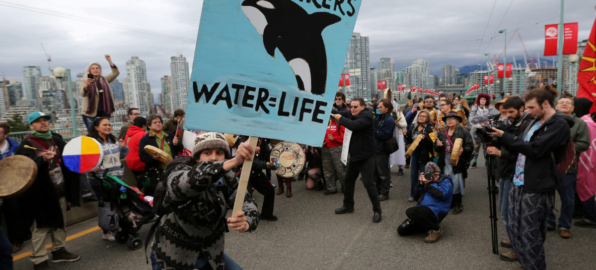 FILE PHOTO: A protester dances with a sign during a march against the proposed expansion of Kinder Morgan's Trans Mountain Pipeline, on the Cambie Street bridge in Vancouver, British Columbia, Canada November 19, 2016. REUTERS/Chris Helgren | Environmentalist May Stop Fighting Trump