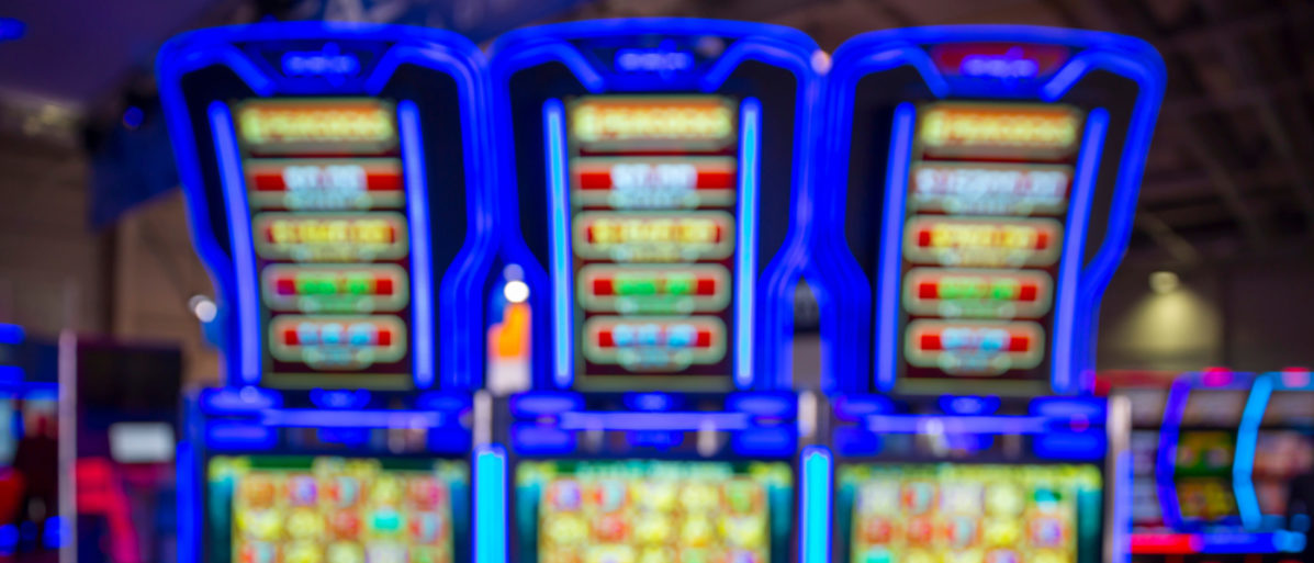 Out of focus blurry image of casino equipment. Blurred slot machines in a casino. Illuminated in blue. (Shutterstock/Belish)