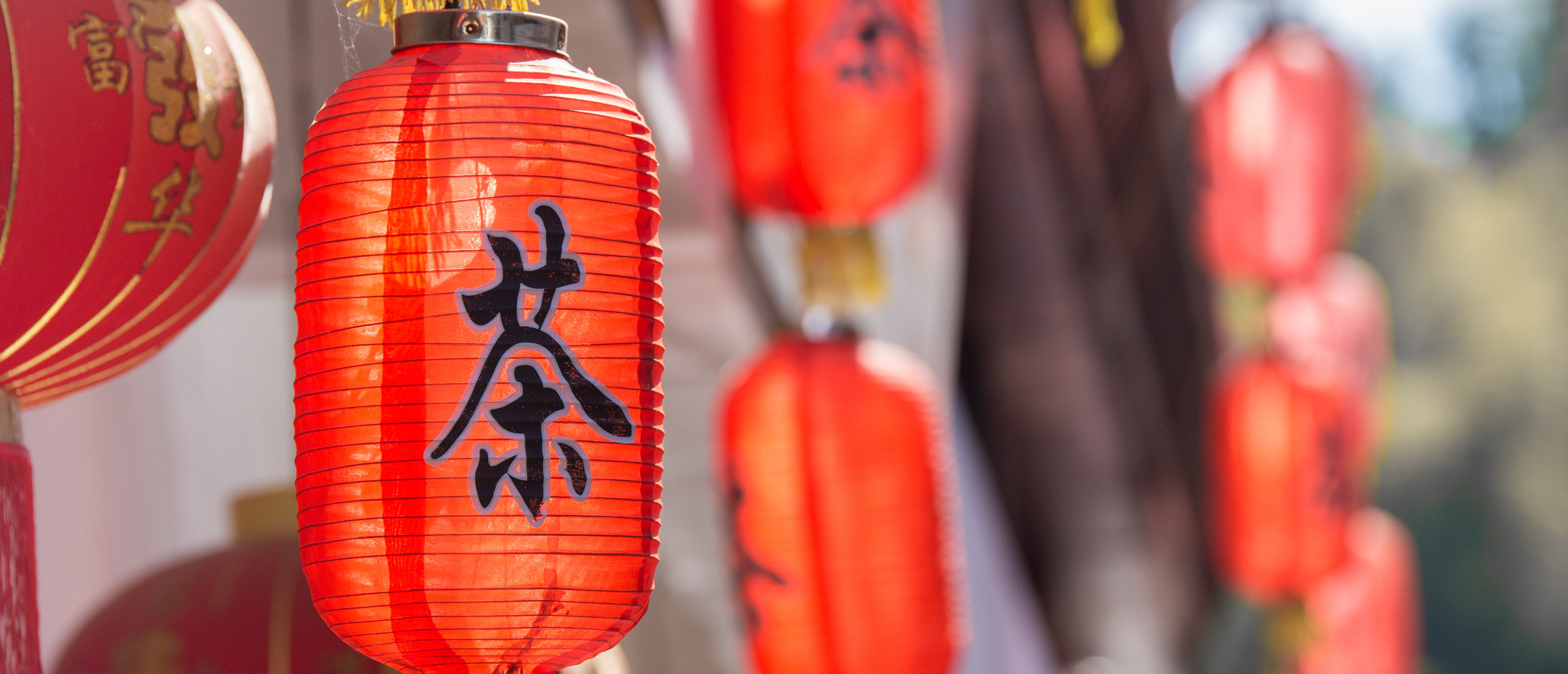 Red Chinese lanterns in an old village with the character for tea outside on a sunny day. Shutterstock