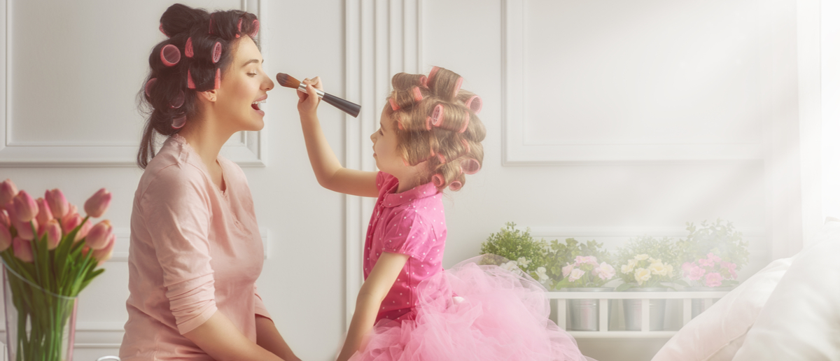 Happy loving family. Mother and daughter are doing hair and having fun. Mother and daughter doing your makeup sitting on the bed in the bedroom. Shutterstock/ Yuganov Konstantin