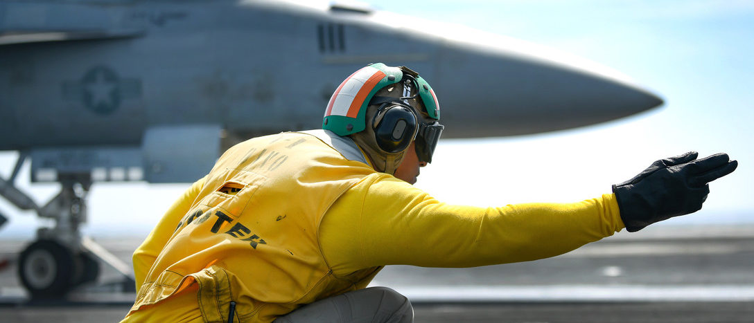 Navy Lt. Ronald Belany signals an F/A-18F Super Hornet to launch on the flight deck of the aircraft carrier USS Theodore Roosevelt in the Persian Gulf, March 19, 2018. Navy photo by Specialist Seaman Michael Hogan