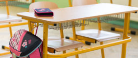 Pictured is a desk in a classroom. (Shutterstock/ABO PHOTOGRAPHY)