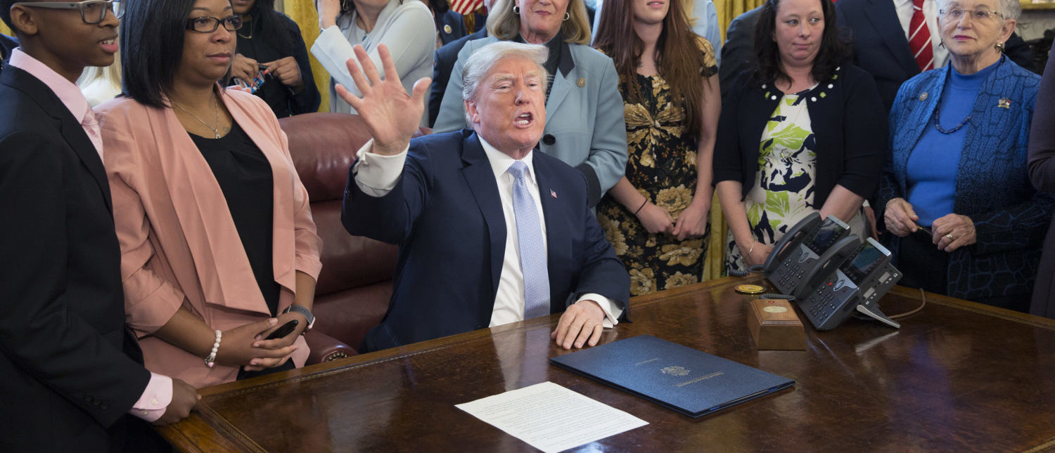 "WASHINGTON, DC - APRIL 11: US President Donald Trump waves goodbye to the media after signing H.R. 1865, the ""Allow States and Victims to Fight Online Sex Trafficking Act of 2017"" at The White House in Washington, DC, April 11, 2018. With Trump are victims and family members of victims of online sex trafficking and members of Congress who helped pass the bill. (Photo by Chris Kleponis-Pool/Getty Images)"