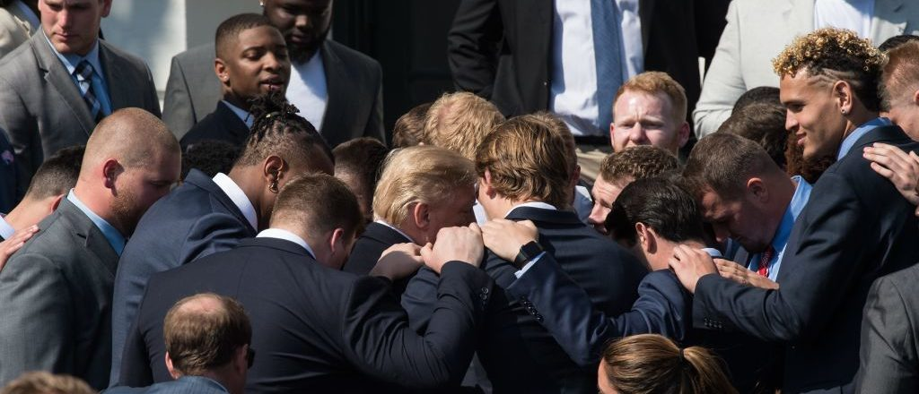 US President Donald Trump prays with members of the 2017 NCAA football national champions the Alabama Crimson Tide at the White House in Washington, DC, on April 10, 2018. / AFP PHOTO / NICHOLAS KAMM        (Photo credit: NICHOLAS KAMM/AFP/Getty Images)