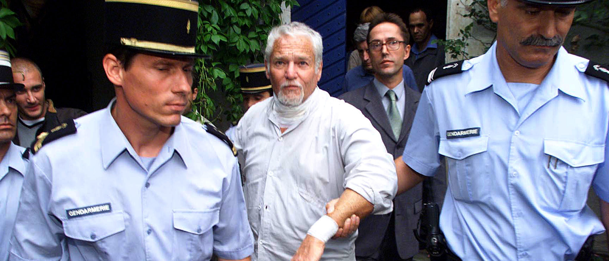 Fugitive former hippie guru Ira Einhorn (C) leaves his home under French gendarme escort in Champagne-Mouton, July 19, 2001, in a possible prelude to his extradition to the United States to face a new trial for the mirder of his girlfriend in 1977. The European Court of Human Rights earlier ruled that Einhorn could be extradited to the USA without further delay to be tried for murder. Einhorn, who slit open his throat in protest last Thursday after losing his final appeal against extradition from France to the U.S. for bludgeoning girlfriend Holly Maddux to death in 1977, promised to go quietly if French police carry out an order to extradite him th the U.S. to stand trial for murder. - Reuters   Earth Day Founder Killed His Girlfriend