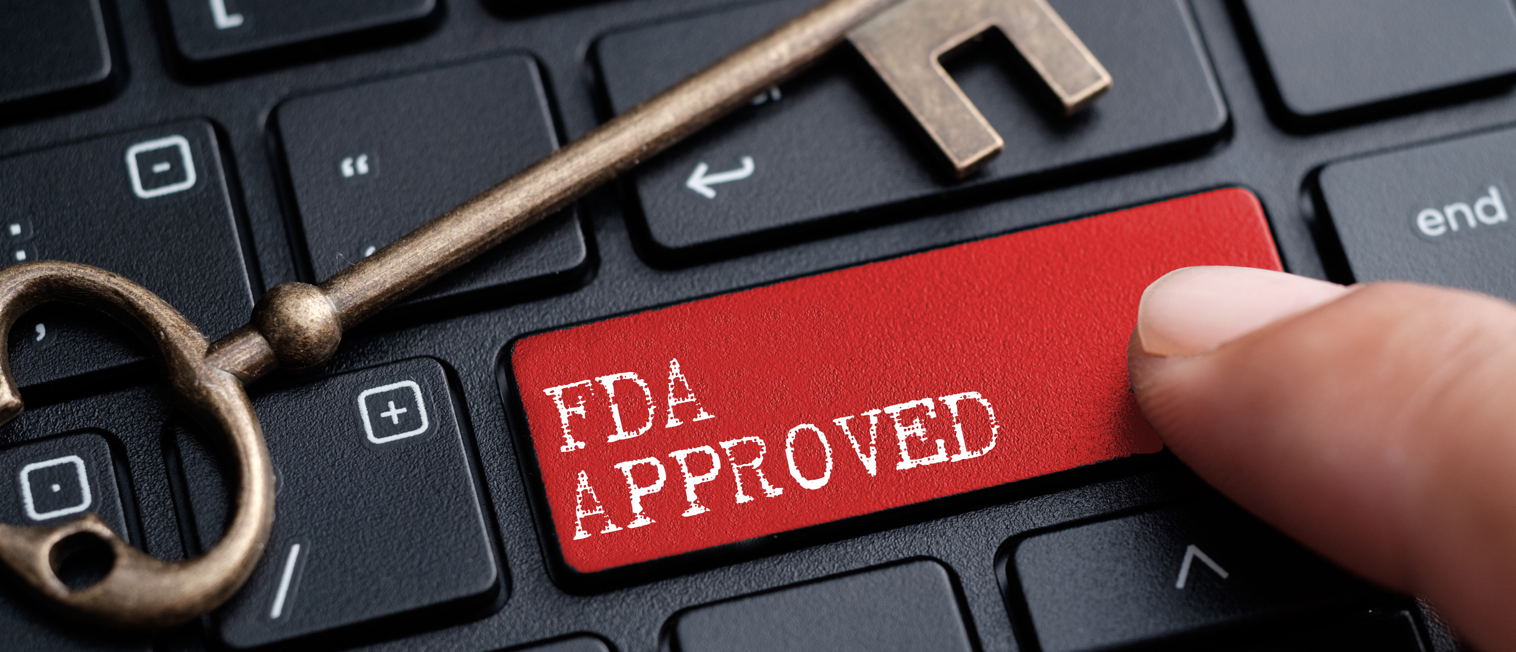 Closed up finger on keyboard with word FDA APPROVED. (Shutterstock)