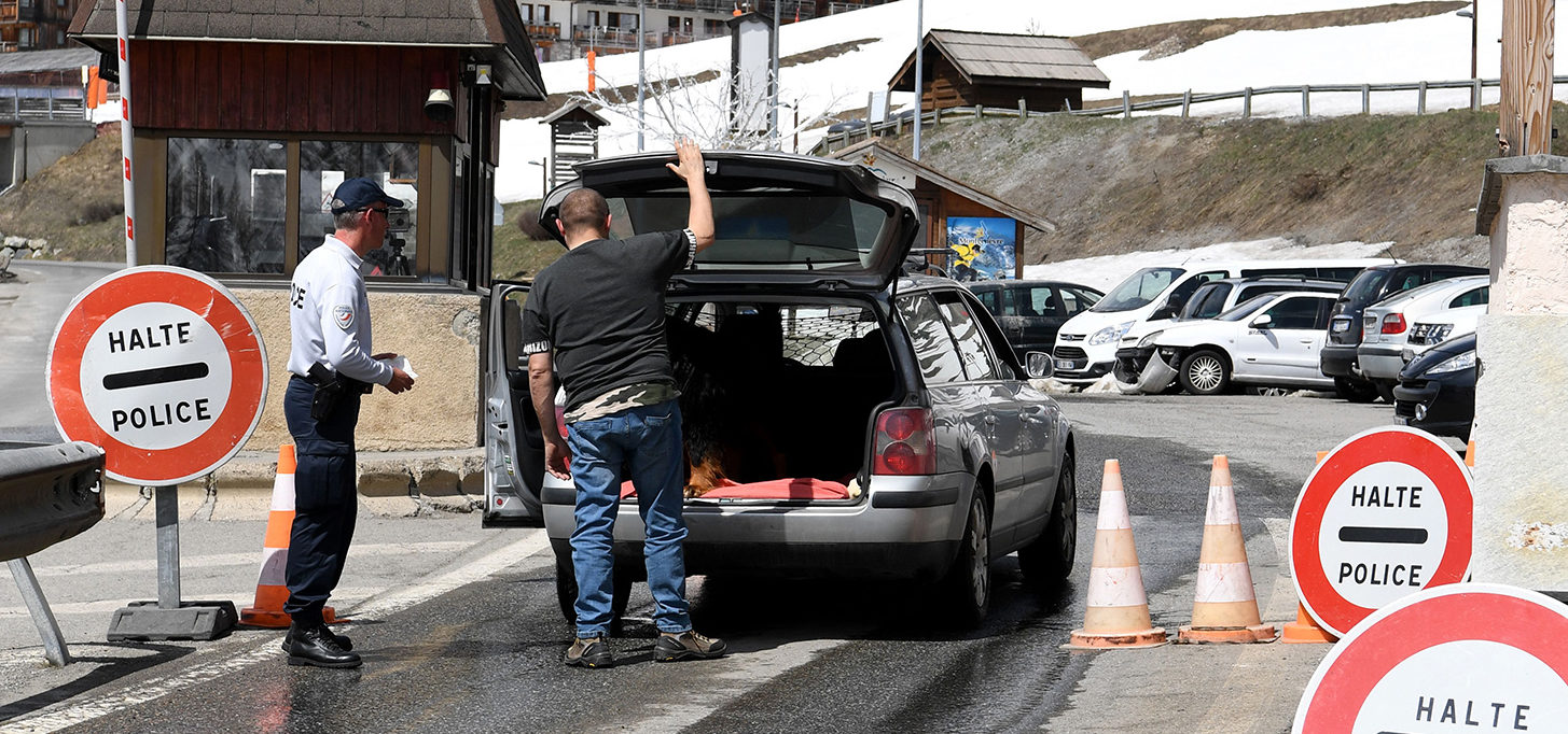 "A man opens the trunk of his car as a French Border Police officer conducts a search at the French checkpoint in Montgenevre on the border between France and Italy in the Alps, on April 23, 2018. - France's interior minister said, on April 22, 2018, he would send ""significant"" security reinforcements to the country's Alpine border with Italy after a weekend of protest actions by pro and anti migrant groups. JEAN-PIERRE CLATOT/AFP/Getty Images"