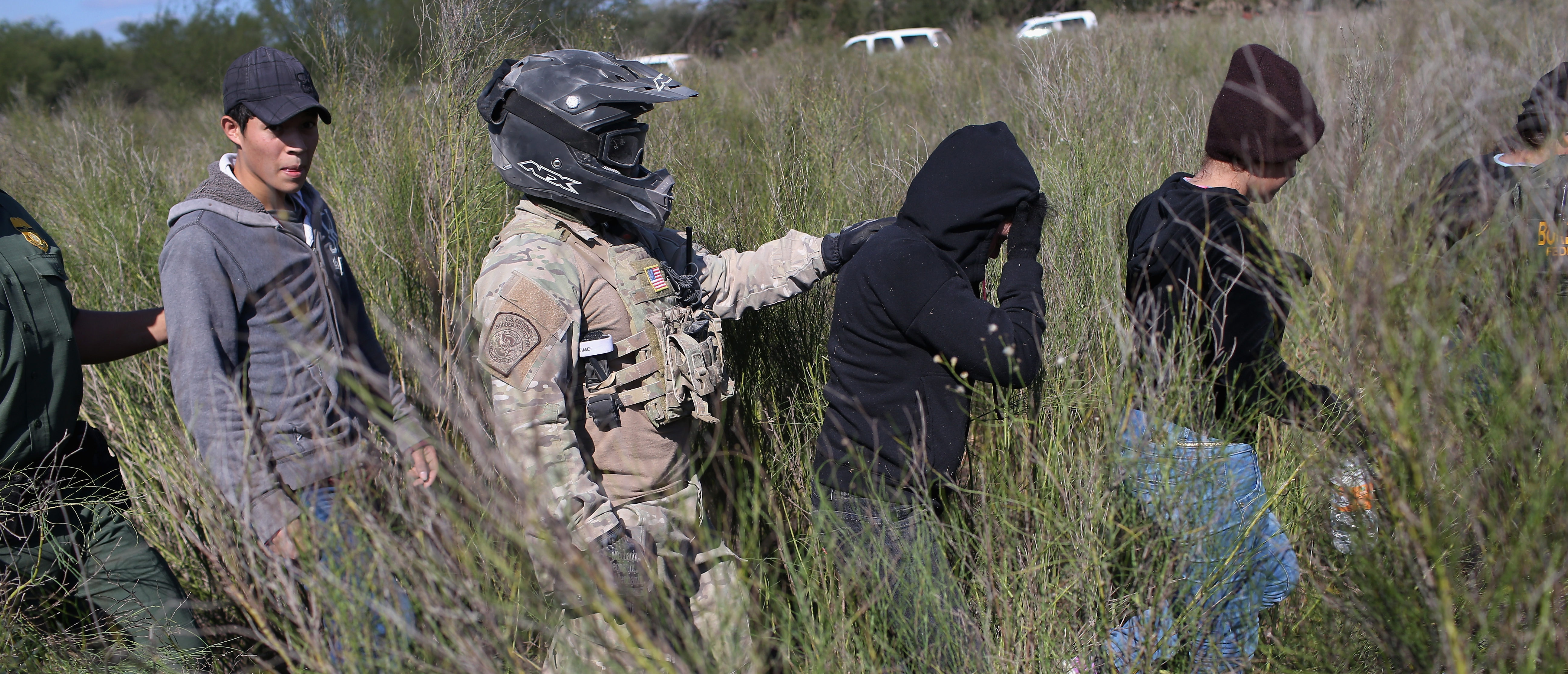 RIO GRANDE CITY, TX - DECEMBER 07: A U.S. Border Patrol agent leads undocumented immigrants after capturing them near the U.S.-Mexico border on December 7, 2015 near Rio Grande City, Texas. Border Patrol agents continue to detain hundreds of thousands of undocumented immigrants trying to avoid capture after crossing into the United States, even as migrant families and unaccompanied minors from Central America cross and turn themselves in to the Border Patrol to seek assylum. (Photo by John Moore/Getty Images)