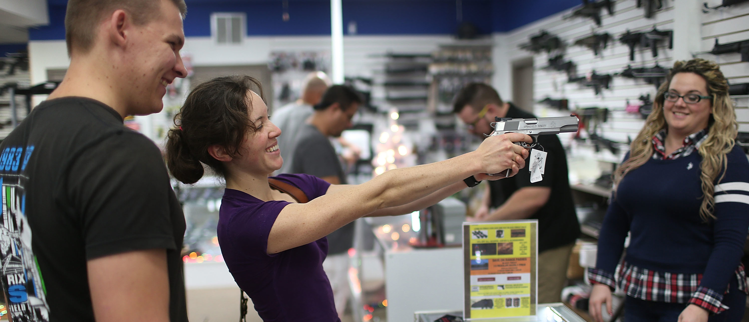 POMPANO BEACH, FL - DECEMBER 23:  Vesta Parks checks out a handgun as she prepares to buy Tim Schneider (L) one as a Christmas present at the National Armory gun store on December 23, 2015 in Pompano Beach, Florida. F.B.I. stats indicate that gun sales have increased dramatically this year, as reports indicate that firearms are a popular choice for a holiday present.  (Photo by Joe Raedle/Getty Images)
