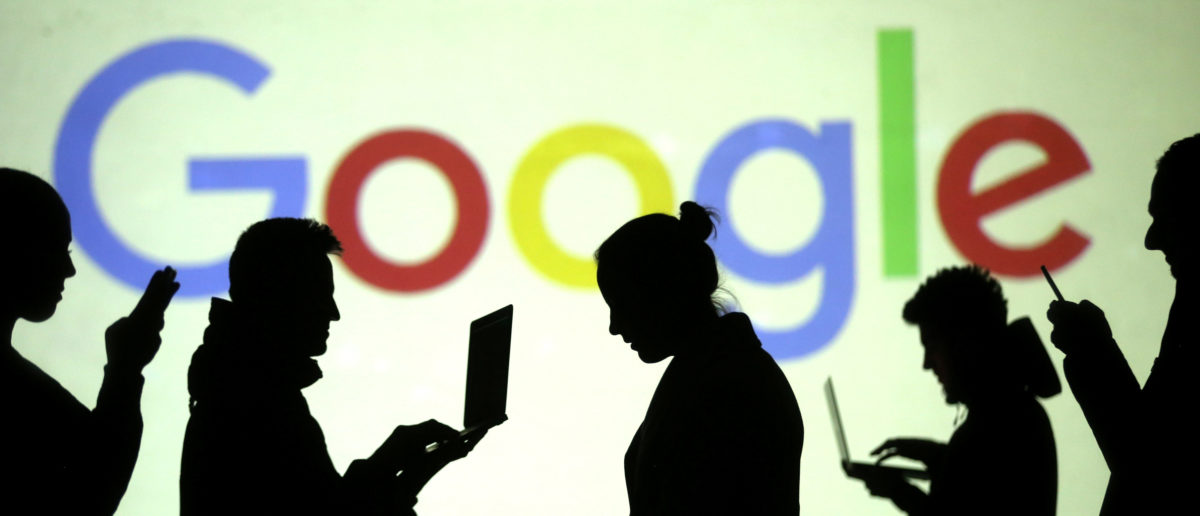 Silhouettes of laptop and mobile device users are seen next to a screen projection of Google logo in this picture illustration taken March 28, 2018. REUTERS/Dado Ruvic/Illustration