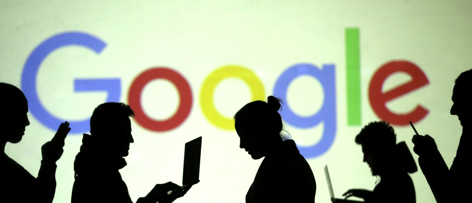 Silhouettes of laptop and mobile device users are seen next to a screen projection of Google logo REUTERS/Dado Ruvic