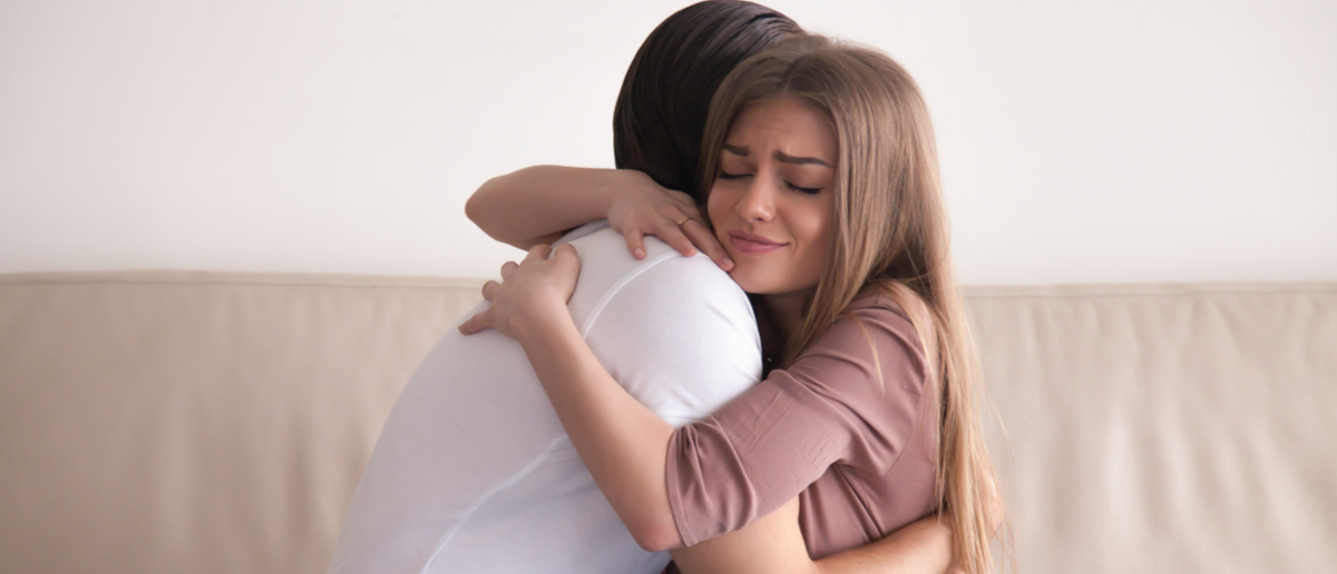 Portrait of emotional young couple hugging each other tightly, boyfriend and girlfriend embracing sitting on couch, reconciliation after argument, love you so much, strong affection in relationships Shutterstock/ Fizkes | NYC Gov't Says A Hug Is Sexual Harassment