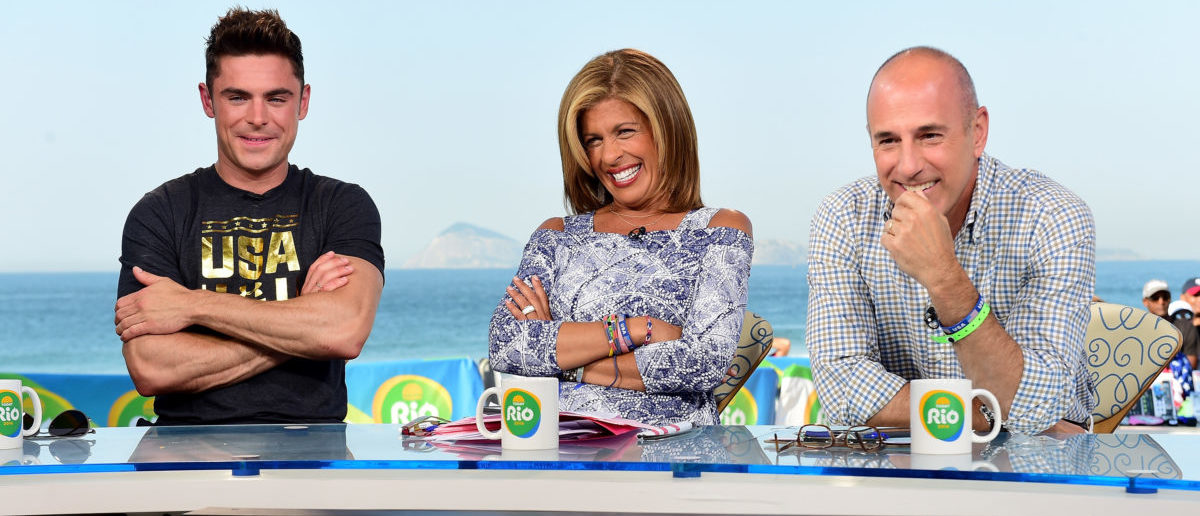 RIO DE JANEIRO, BRAZIL - AUGUST 17:  (BROADCAST - OUT)  Actor Zac Efron with Hoda Kotb and Matt Lauer on the Today show set on Copacabana Beach on August 17, 2016 in Rio de Janeiro, Brazil.  (Photo by Harry How/Getty Images)