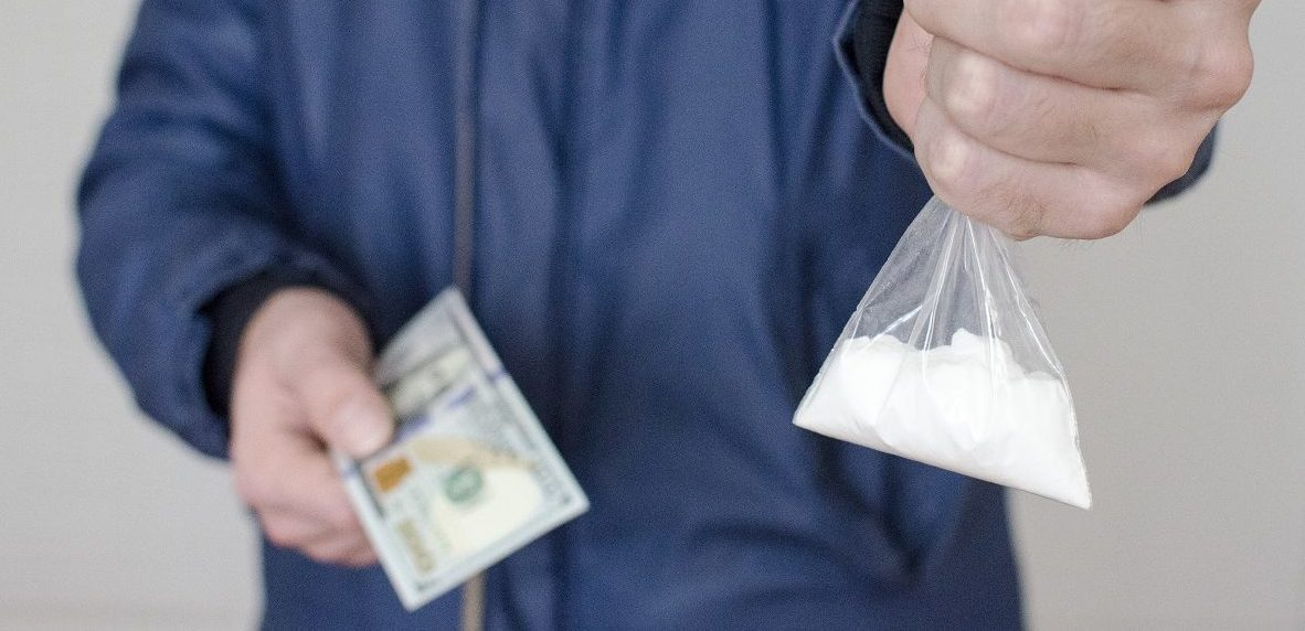 White man holds out a packet of drugs and takes money. (Zhenzhirov/Shutterstock)
