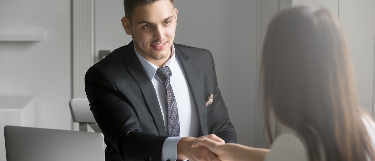 Friendly smiling businessman and businesswoman handshaking over the office desk after pleasant talk and effective negotiation, good relationship, making deal, hiring Business concept photo