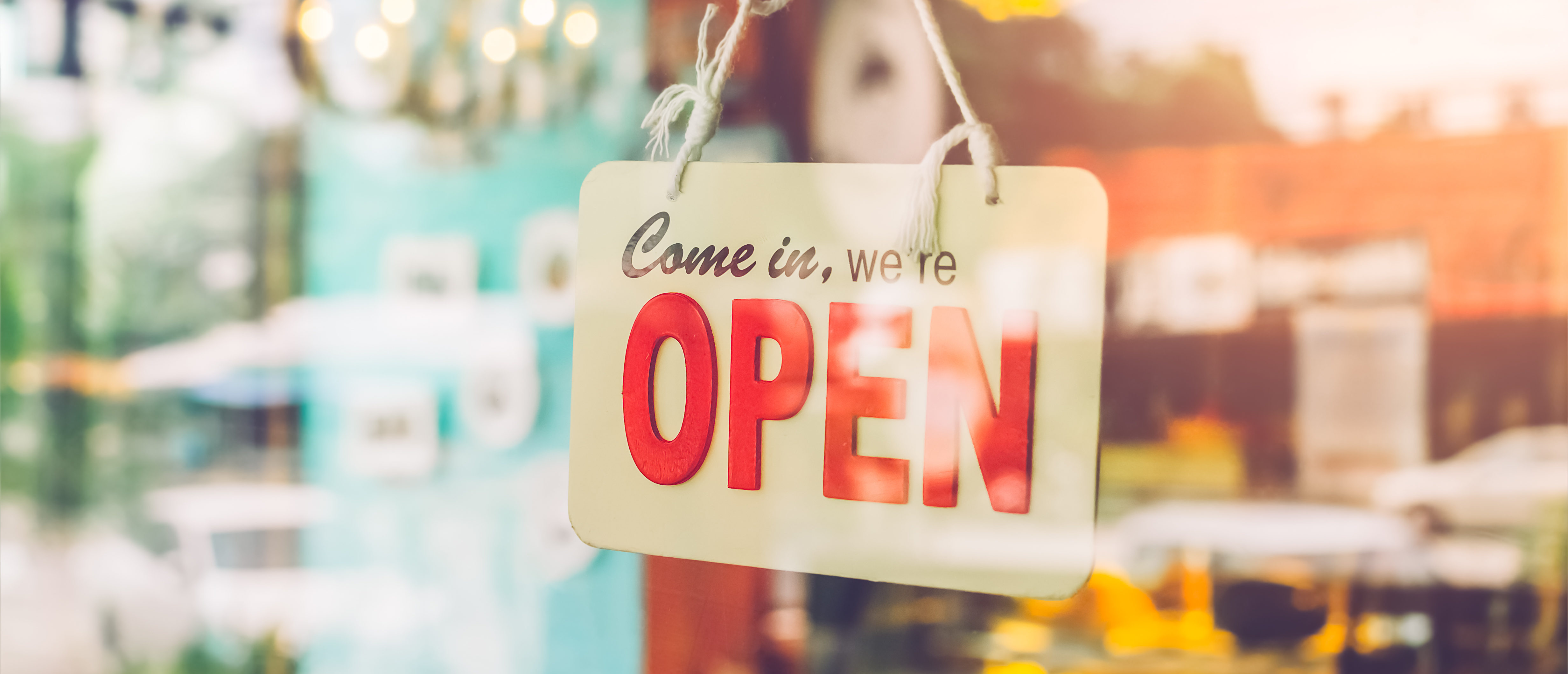 Open sign broad through the glass of door in cafe. Business service and food concept. (Shutterstock)