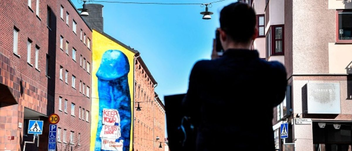 """Banners reading """"Keep your penis inside"""" are fixed on a mural made by Swedish artist Carolina Falkholt, showing a giant blue penis painted on the wall of a residential building in Stockholm, on April 14, 2018. / AFP PHOTO / TT News Agency / Anders WIKLUND / Sweden"""