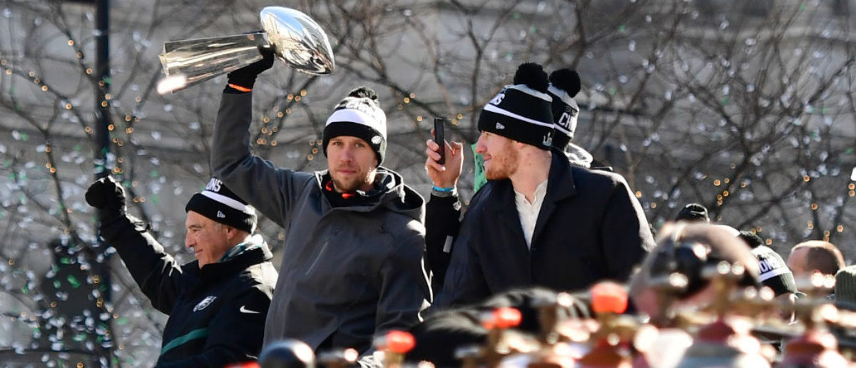 PHILADELPHIA, PA - FEBRUARY 08: (L-R) Team owner Jeffrey Lurie, with quarterbacks Nick Foles #9, Nate Sudfeld #7 (hand) and Carson Wentz #11 of the Philadelphia Eagles, acknowledge fans as Foles hoists the Vince Lombardi Trophy atop a parade bus during festivities on February 8, 2018 in Philadelphia, Pennsylvania. The city celebrated the Philadelphia Eagles' Super Bowl LII championship with a victory parade. (Photo by Corey Perrine/Getty Images)