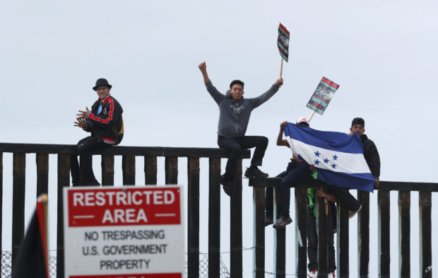 People climb the border wall fence as a caravan of migrants and supporters reached the United States-Mexico border near San Diego, California, U.S., April 29, 2018 Reuters