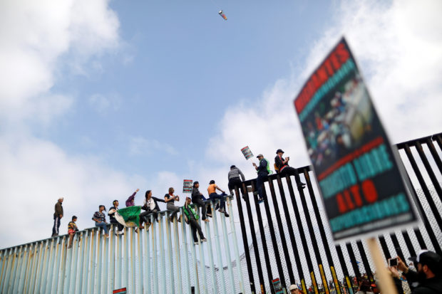 Members of a caravan of migrants from Central America and activists sit on the border fence between Mexico and the U.S., as a part of a demonstration prior to preparations for an asylum request in the U.S., in Tijuana, Mexico April 29, 2018. REUTERS/Edgard Garrido