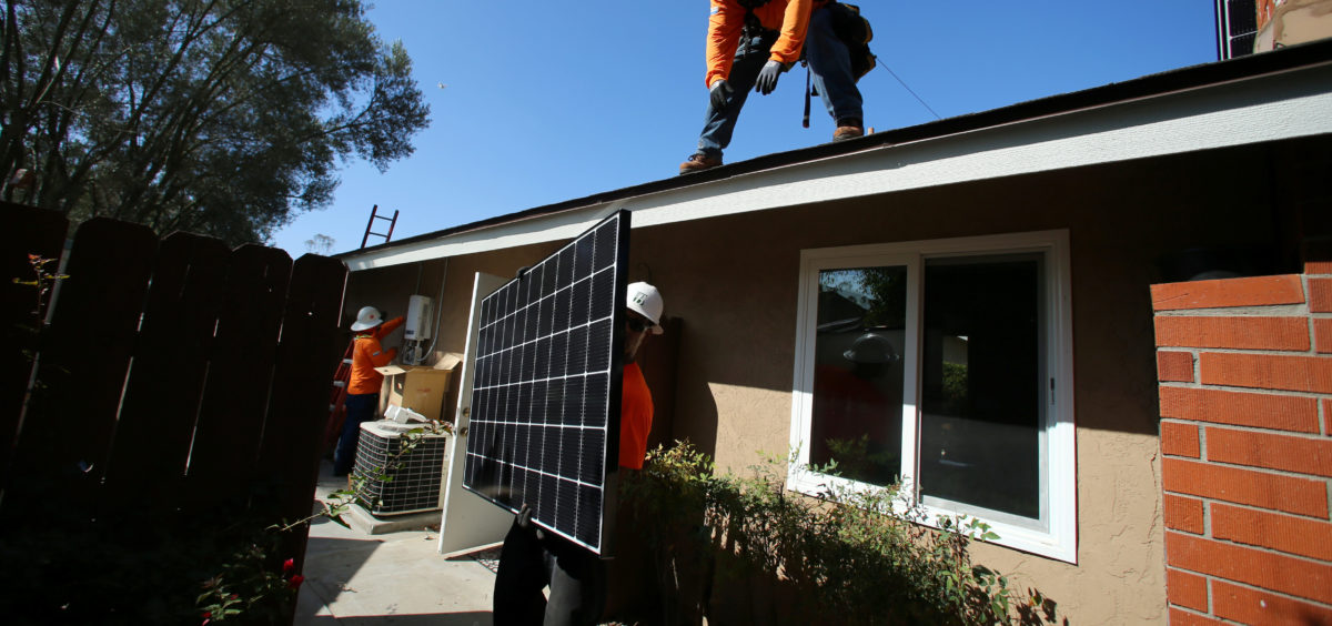 Workers lift a solar panel onto a roof during a residential solar installation in Scripps Ranch, San Diego, California