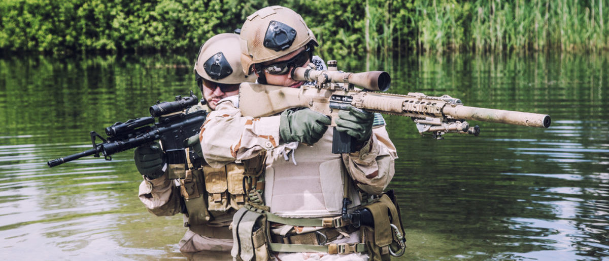 Navy SEALs crossing the river with weapons (SHUTTERSTOCK: By Getmilitaryphotos)