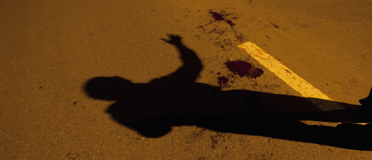 The shadow of a police official is seen near a blood stain after an unidentified gunman was injured by security officials and arrested in Islamabad August 15, 2013. The armed man demanding the establishment of Islamic rule in Pakistan opened fire in the heart of Islamabad on Thursday and was arrested hours later after a standoff with police that was broadcast live on television. REUTERS/Mian Khursheed