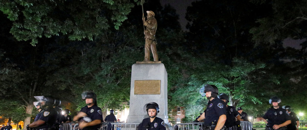 Police wearing riot gear guard a statue of a Confederate soldier nicknamed Silent Sam on the campus of the University of North Carolina during a demonstration for its removal in Chapel Hill, North Carolina, U.S. August 22, 2017. REUTERS/Jonathan Drake     TPX IMAGES OF THE DAY | Confederate Memorials Under Attack