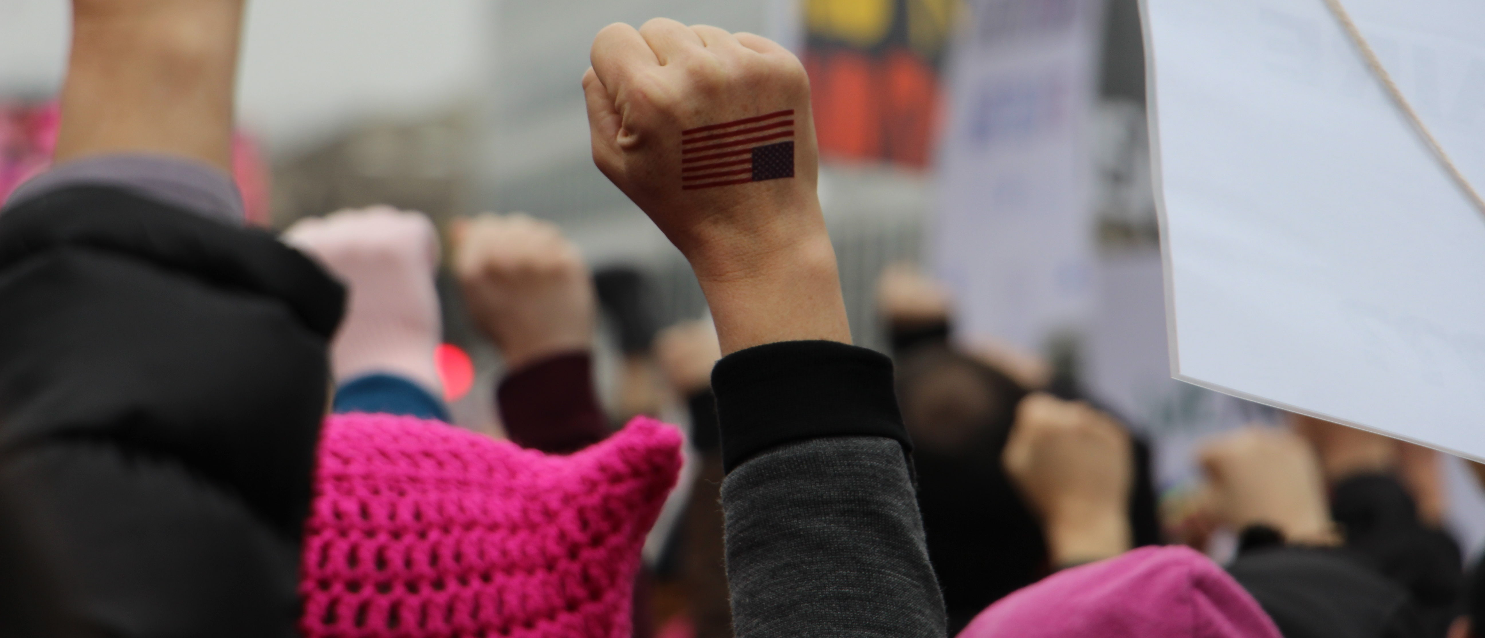 Woman's fist with US flag raised in the air at Women's March in Washington DC. (Shutterstock)