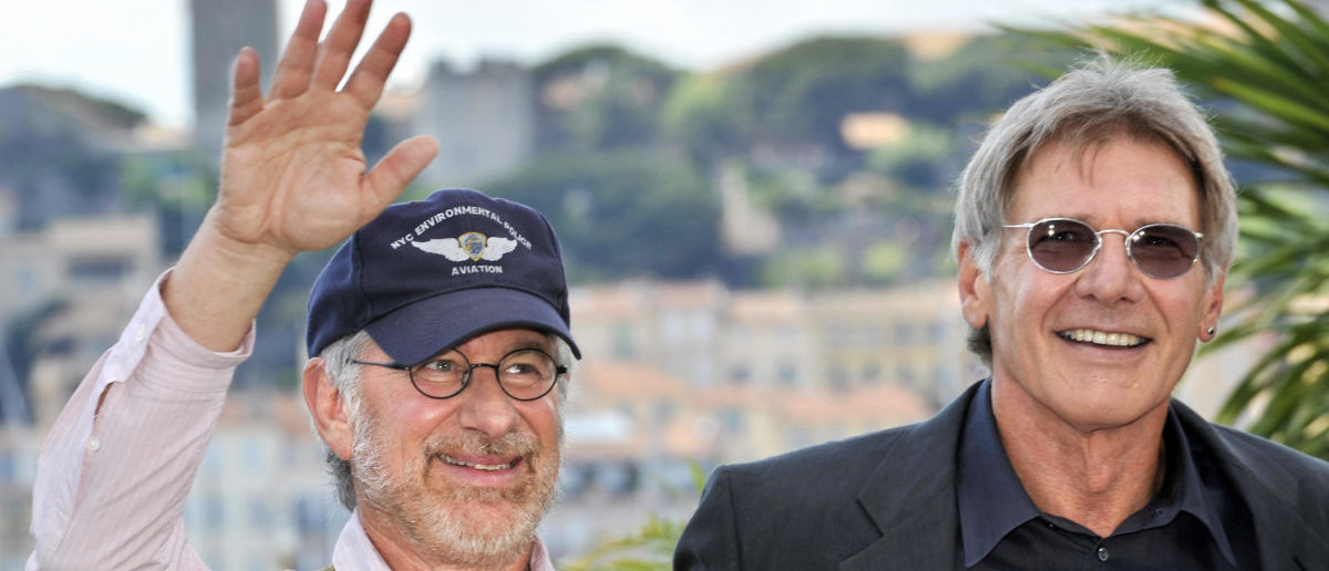 """US director Steven Spielberg (L) waves as he poses with actor Harrison Ford during a photocall for his film 'Indiana Jones 4' at the 61st Cannes International Film Festival on May 18, 2008 in Cannes, southern France. Indiana Jones rides into Cannes on May 18, 2008 on his most perilous quest, facing a whipping by the critics or the Holy Grail of success. The world premiere of the latest instalment in the """"Indiana Jones"""" saga, the first in 19 years, is the hottest ticket at this year's Cannes film festival. AFP PHOTO / Anne-Christine Poujoulat (Photo credit should read ANNE-CHRISTINE POUJOULAT/AFP/Getty Images)"""