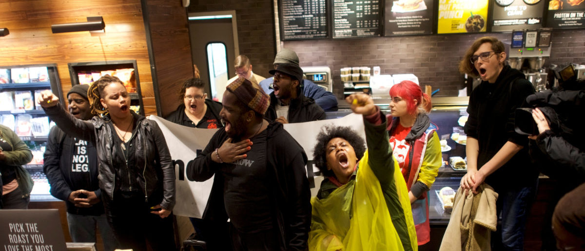 Protesters demonstrate inside a Center City Starbucks, where two black men were arrested, in Philadelphia, Pennsylvania, U.S., April 16, 2018. REUTERS/Mark Makela