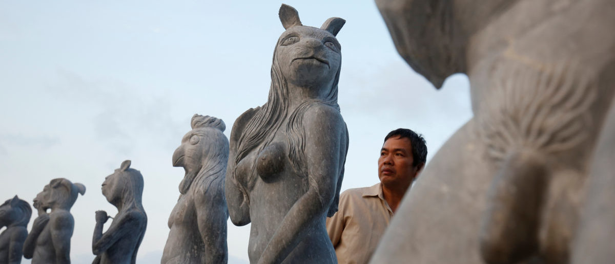 A man watches godlike sculptures with animal heads and human genitalia at Hon Dau resort in Hai Phong city, east of Hanoi, Vietnam April 5, 2018. Picture taken April 5, 2018. REUTERS/Kham