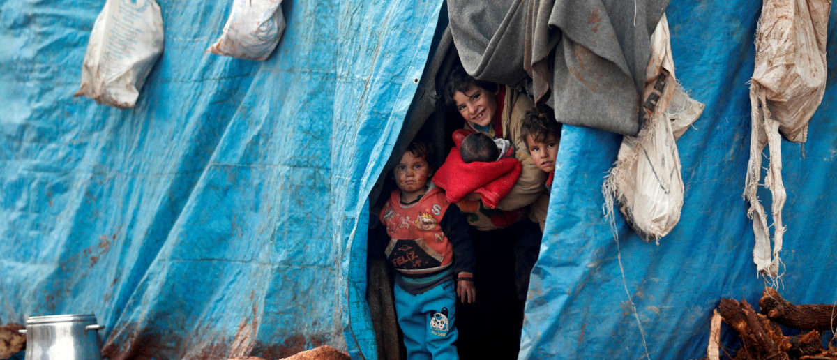 Displaced Syrian children look out from their tents at Kelbit refugee camp, near the Syrian-Turkish border, in Idlib province, Syria January 17, 2018. Picture taken January 17, 2018. REUTERS/Osman Orsal