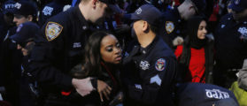 New York Police Department officers detain organizer Tamika Mallory as she takes part in a 'Day Without a Woman' march on International Women's Day in New York, U.S., March 8, 2017. REUTERS/Lucas Jackson