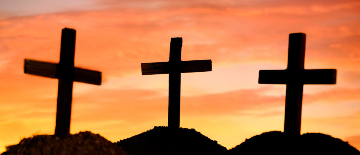 Three crosses stand on a hill. (Shutterstock/Doidam 10)