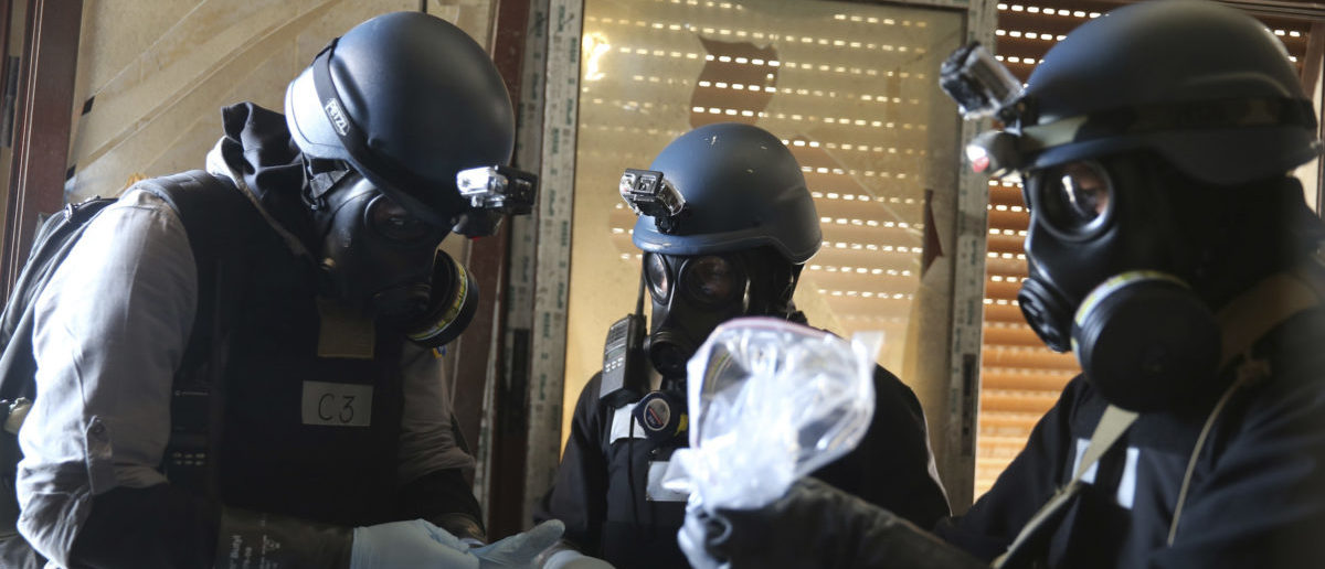 A U.N. chemical weapons expert, wearing a gas mask, holds a plastic bag containing samples from one of the sites of an alleged chemical weapons attack in the Ain Tarma neighbourhood of Damascus August 29, 2013. A team of U.N. experts left their Damascus hotel for a third day of on-site investigations into apparent chemical weapons attacks on the outskirts of the capital. Activists and doctors in rebel-held areas said the six-car U.N. convoy was scheduled to visit the scene of strikes in the eastern Ghouta suburbs. REUTERS/Mohamed Abdullah | Chemical Weapons Attacks Common In Syria